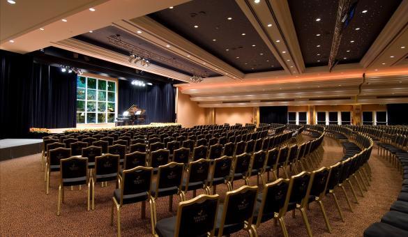 salle de séminaire en théâtre avec estrade et un piano dessus. Parfait pour vos séminaires en Wallonie