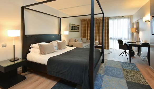chambre double avec lit en baldaquin et couvre-lit noir. Bureau avec chaise et un canapé
