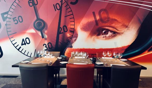 table de restaurant avec mur représentant un chrono et une personne avec casque