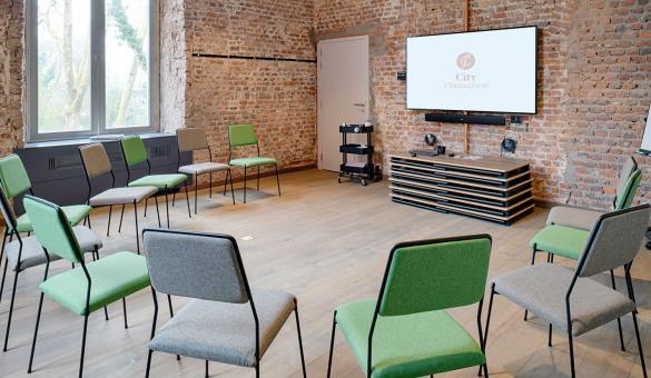 Salle de sous-commission avec mur en briques et chaises en demi-cercle face à un écran plat. Parfait pour vos événements d'affaires en Wallonie
