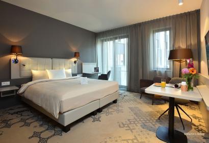 chambre avec lit double et mur taupe dans un hôtel d'affaires à Louvain-La-Neuve.